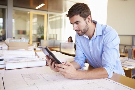 arquitecto: Arquitecto de sexo masculino con la tableta digital Estudiar los planes en la oficina