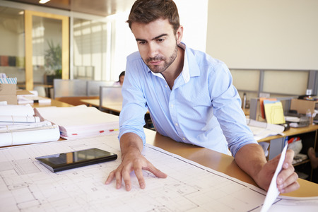 open plan office: Male Architect With Digital Tablet Studying Plans In Office