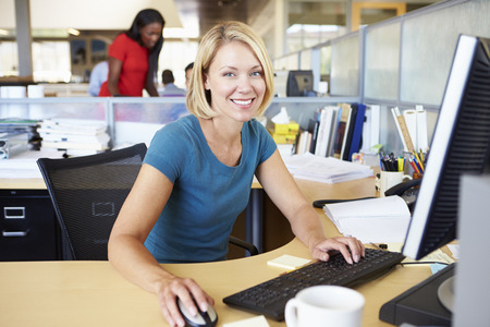 Woman Working At Computer In Modern Office photo