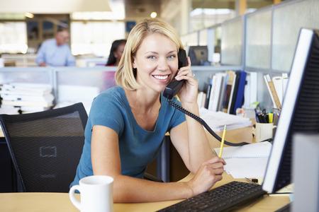 忙しい現代オフィスでの携帯電話上の女性 写真素材