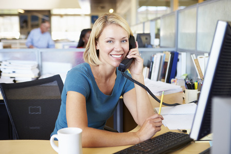 charming business lady: Woman On Phone In Busy Modern Office Stock Photo