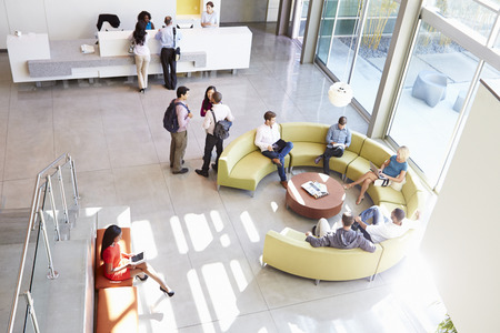 BUSY OFFICE: Reception Area Of Modern Office Building With People