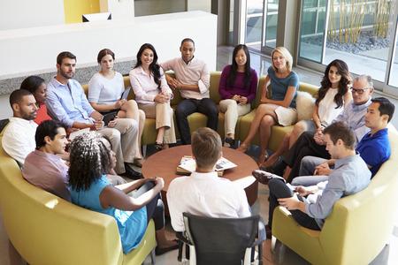 一緒に会議を持つ多文化事務所スタッフ座って