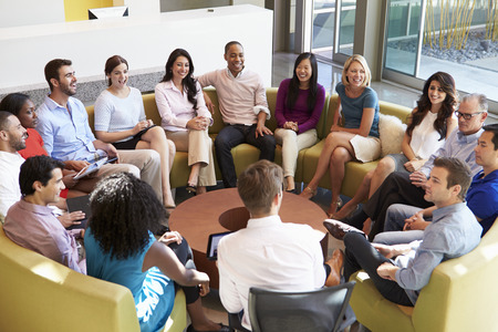 Multi-Cultural Office Staff Sitting Having Meeting Together Imagens