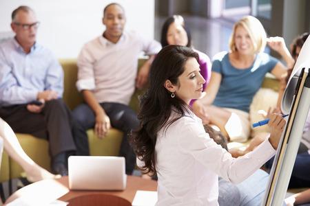 ビジネスウーマン職場の同僚にプレゼンテーションを作る