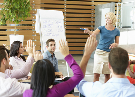 asking: Businesswoman Making Presentation To Office Colleagues