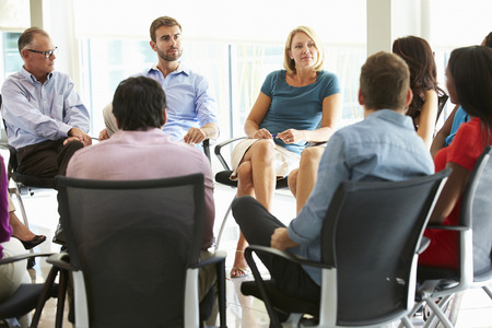 Multi-Cultural Office Staff Sitting Having Meeting Together Stockfoto