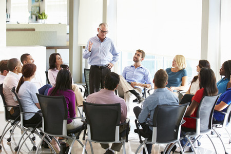 round chairs: Businessman Addressing Multi-Cultural Office Staff Meeting