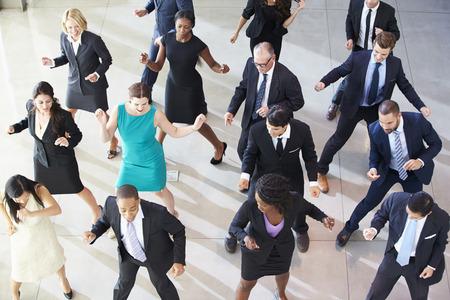 gl�ckliche menschen: Obenliegende Ansicht der Gesch�ftsleute Tanzen im B�ro Lobby Lizenzfreie Bilder
