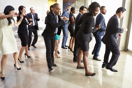 danza moderna: Empresarios y empresarias Dancing In Office Lobby Foto de archivo