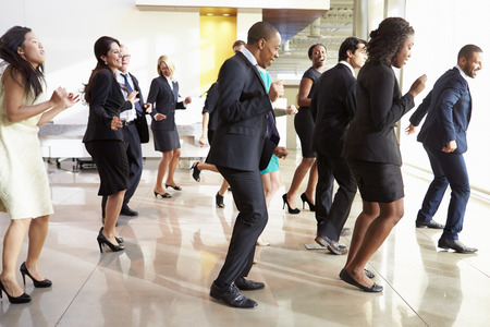Businessmen And Businesswomen Dancing In Office Lobby photo