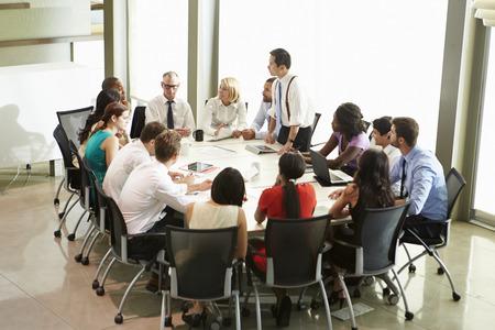 Businessman Addressing Meeting Around Boardroom Table photo
