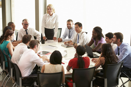 woman boss: Businesswoman Addressing Meeting Around Boardroom Table