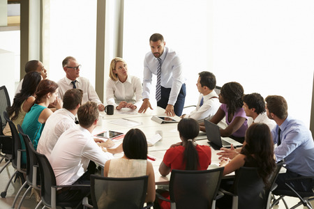 employers: Businessman Addressing Meeting Around Boardroom Table