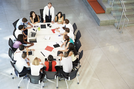 Businessman Addressing Meeting Around Boardroom Table photo