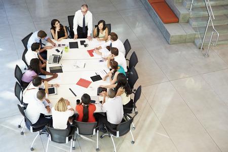 addressing: Businessman Addressing Meeting Around Boardroom Table