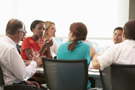 mixed race: Group Of Businesspeople Meeting Around Boardroom Table Stock Photo