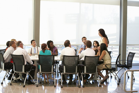 Businesswoman Addressing Meeting Around Boardroom Table