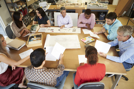 architecture plans: Group Of Architects Sitting Around Table Having Meeting