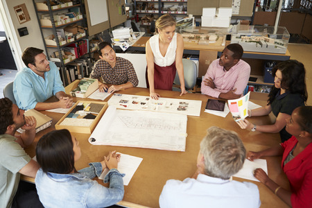 Female Boss Leading Meeting Of Architects Sitting At Table photo