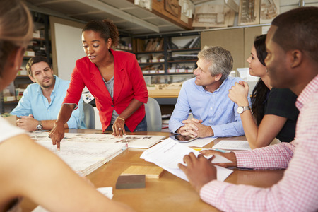 woman boss: Female Boss Leading Meeting Of Architects Sitting At Table Stock Photo