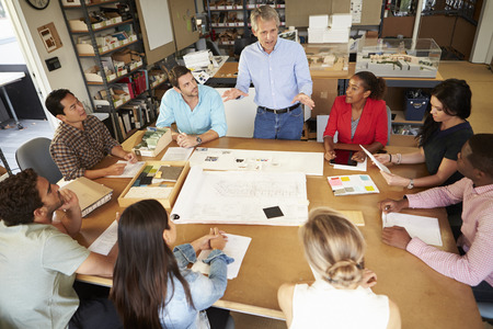 Group Of Architects Sitting Around Table Having Meeting photo