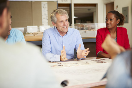 female boss: Male Boss Leading Meeting Of Architects Sitting At Table