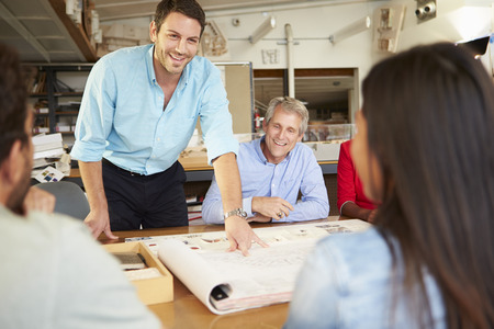 people: Male Boss Leading Meeting Of Architects Sitting At Table