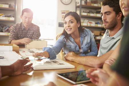architect office: Five Architects Sitting Around Table Having Meeting Stock Photo