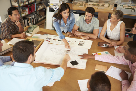 architect office: Female Boss Leading Meeting Of Architects Sitting At Table Stock Photo