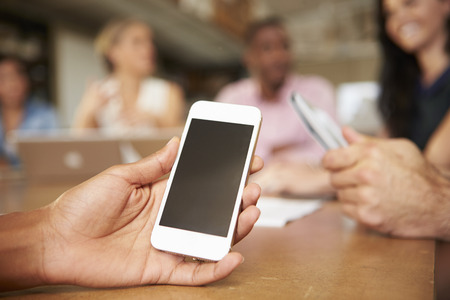 to phone: Mobile Phone Being Used By Architect In Meeting