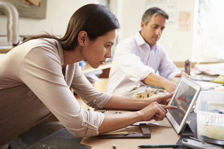 asian architect: Two Architects Making Models In Office Using Digital Tablet Stock Photo