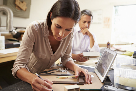 Two Architects Making Models In Office Using Digital Tablet Stock Photo