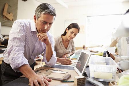 personas trabajando: Dos Arquitectos hacer modelos en oficina usando la tableta digital