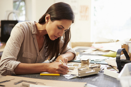 architect office: Female Architect Making Model In Office