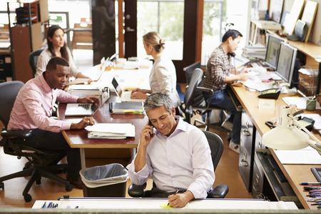 personas trabajando oficina: Interior de la oficina del Arquitecto Busy Con trabajo de los servicios