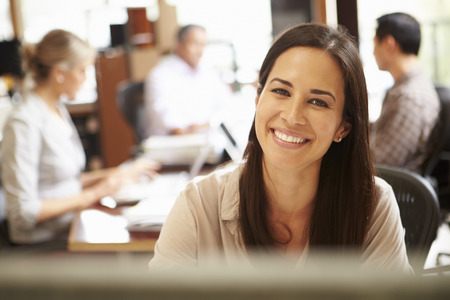 Businesswoman Working At Desk With Meeting In Background Stockfoto