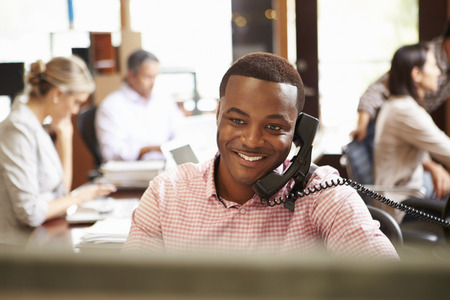 black business men: Businessman On Phone At Desk With Meeting In Background