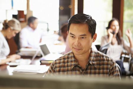 バック グラウンドでの会議で机で働くビジネスマン