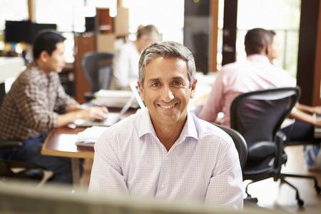 ležérní: Obchodník pracující u stolu s setkání v pozadí Reklamní fotografie