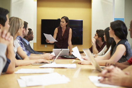 addressing: Female Boss Addressing Meeting Around Boardroom Table