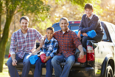 Fathers With Sons Sitting In Truck On Camping Holiday photo