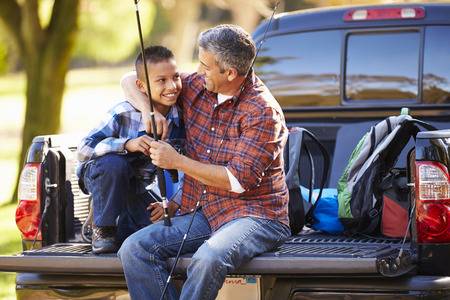 camping equipment: Father And Son Sitting In Pick Up Truck On Camping Holiday