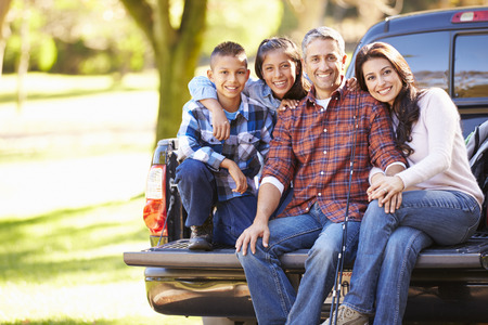 Family Sitting In Pick Up Truck On Camping Holiday Archivio Fotografico