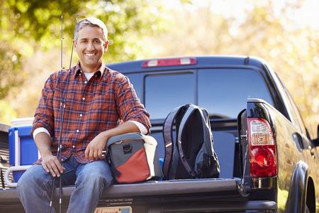 hombre pescando: Retrato del hombre que se sienta en Pick Up Camión en acampada