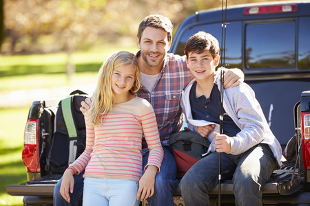 10 12 years: Father And Children Sitting In Truck On Camping Holiday