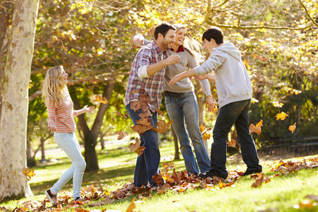 boy 12 year old: Family Throwing Autumn Leaves In The Air