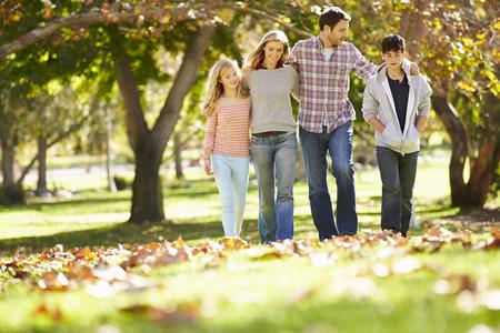 Família que anda através Outono Woodland