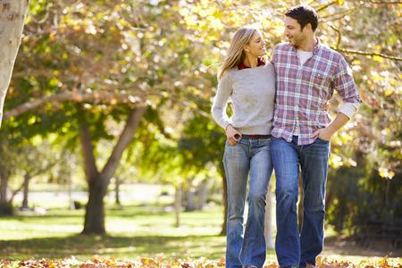 parejas caminando: Pares románticos que recorren a través del arbolado del otoño