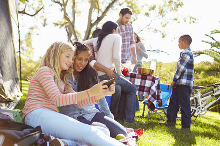 boy 12 year old: Two Girls Using Mobile Phone On Family Camping Holiday
